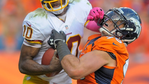 Washington Redskins quarterback Robert Griffin III (10) stiff arms Denver Broncos defensive end Derek Wolfe (95) in the fourth quarter of an NFL football game, Sunday, Oct. 27, 2013, in Denver. (AP Photo/Jack Dempsey)