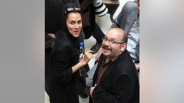 FILE - In this April 11, 2013 file photo, Jason Rezaian, right, an Iranian-American correspondent for the Washington Post, and his wife Yeganeh Salehi, an Iranian correspondent for the Abu Dhabi-based daily newspaper, The National, smile as they attend a presidential campaign of President Hassan Rouhani in Tehran, Iran. The family of Rezaian who is detained in Iran says authorities there have allowed him to hire a lawyer after more than seven months behind bars, though it is not the attorney they had hoped for. Rezaian was detained in Tehran on July 22, 2014 along with Salehi, and two photojournalists. Rezaian, who was born and spent most of his life in the United States, is the only one of the four still behind bars. (AP Photo/Vahid Salemi, File)
