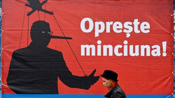 """A woman walks backdropped by a campaign poster of Klaus Iohannis leader of Romania's centre-right Liberals and mayor of the Transylvanian city of Sibiu, showing a mock representation of Prime Minister and candidate of the ruling Social Democracy Party (PSD) together with the texts """"Stop the lying!"""" and """"Choose the normal Romania!"""",  in Bucharest, Romania, Monday, Nov. 10, 2014. Top party lieutenants in Ponta's Social Democratic Party, regular party members and other supporters have been convicted or are being probed for corruption, but Ponta appears unscathed. An election runoff will be held on Nov. 16., to elect a new leader as President Traian Basescu steps down after 10 years in office. (AP Photo/Octav Ganea, Mediafax) ROMANIA OUT"""