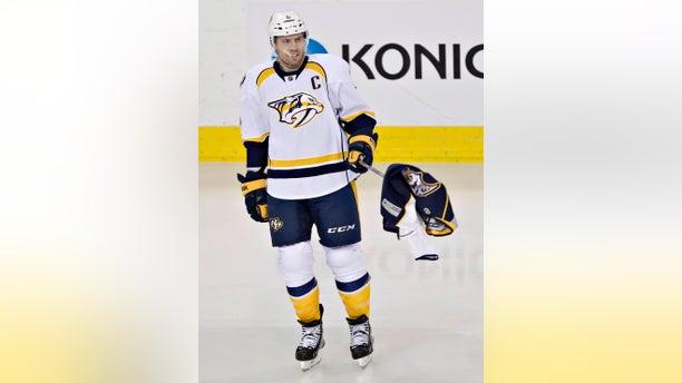 Nashville Predators Shea Weber (6) picks up a Predators jersey thrown on the ice by a fan during third period of an NHL hockey game in Edmonton, Alberta, Sunday, Jan. 26, 2014. (AP Photo/The Canadian Press, Jason Franson)