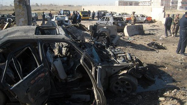 Mar. 20, 2012: People and security forces inspect the scene of a car bomb attack in Kirkuk.