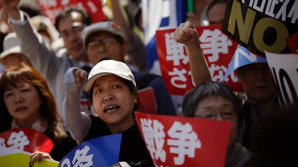 In this Thursday, May 14, 2015 photo, people stage an anti-war rally in protest against controversial bills intended to expand Japan's defense role at home and internationally, pushed by Japanese Prime Minister Shinzo Abe, outside Abe's official residence in Tokyo. Abe's pledge to the U.S. to increase Japan's military contribution internationally is facing more questions about potential conflicts with the nation's pacifist Constitution. Opposition lawmakers demanded answers from key Cabinet members at a hearing Wednesday, June 10, 2015 after three prominent constitution experts — including one chosen by Abe's ruling party — unanimously told a parliamentary committee last week that legislation allowing Japanese troops to defend foreign militaries would violate the war-renouncing Article 9 of Japan's postwar constitution. (AP Photo/Eugene Hoshiko)