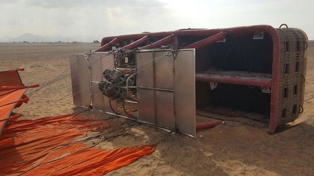 This Saturday, Jan. 14, 2017, released by Sharjah police, and made available today, shows a balloon that was carrying European and Asian tourists after it struck the ground as it flew over the desert near the small town of al-Madam, United Arab Emirates. Investigators in the UAE are looking into what caused a hot-air balloon to abruptly drop from the sky, injuring six tourists onboard. (Sharjah Police via AP)
