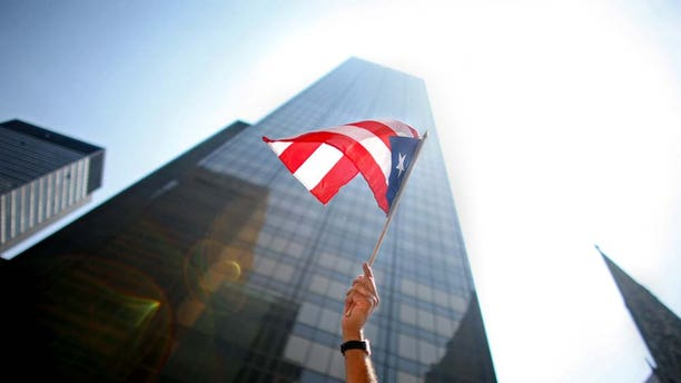 NEW YORK CITY - JUNE 8:  A participant waves a flag in the annual Puerto Rico Day Parade June 8, 2008 in New York City. The parade honoring Puerto Ricans is an annual New York City tradition and takes place along Fifth Avenue.  (Photo by Yana Paskova/Getty Images)