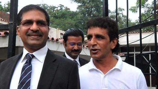 Pakistani umpire Asad Rauf (R) leaves with his legal adviser Syed Ali Zafar after a press conference in Lahore on September 27, 2013.