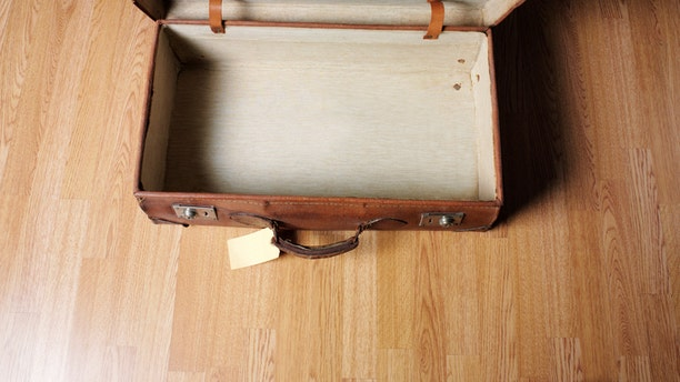Empty old open leather suitcase with old luggage label, wooden floor, and copy space