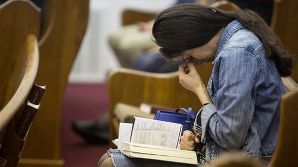 April 6, 2014: Kathy Abad, a military wife, prays for the victims and families affected by the Fort Hood shooting during a memorial service at the Tabernacle Baptist Church.