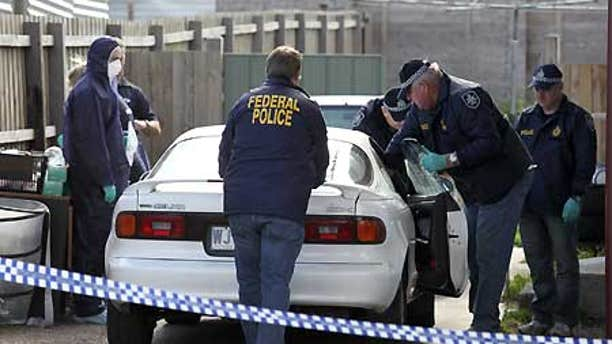 Aug. 4: Police search a car at a Melbourne suburb after a pre-dawn raid at one of 19 locations.