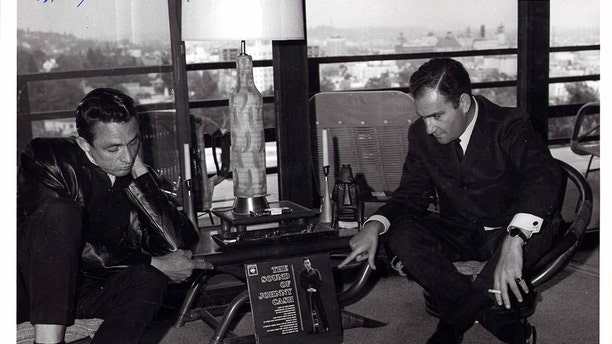 """Johnny Cash and Saul Holiff in Saul's Hollywood apartment, 1962. They are pointing at Johnny's album, """"The Sound of Johnny Cash""""."""