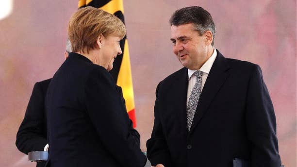 Former German Minister for Economic Affairs and Energy and new Foreign Minister Sigmar Gabriel shakes hands with German Chancellor Angela Merkel after he received his notices of dismissal and documents of appointment by German President Joachim Gauck in Berlin, Germany, Friday, Jan. 27, 2017. (AP Photo/Michael Sohn)