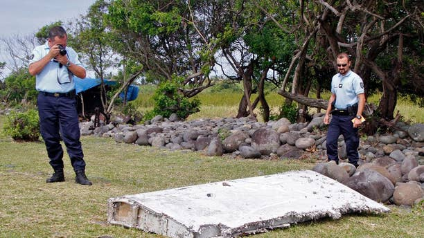 FILE - In this July 29, 2015 file photo, French police officers look over a piece of debris from a plane in Saint-Andre, Reunion Island. The wing was later found to be from missing Malaysia Airlines Flight 370 that went missing March 8, 2014, with 239 people aboard while flying from Kuala Lumpur to Beijing. Analysis of a genuine Boeing 777 wing flap has reaffirmed experts' opinion that a missing Malaysian airliner most likely crashed north of an abandoned search area in the Indian Ocean, officials said Friday, April 21, 2017. The search for Malaysia Airlines Flight 370 ended in January after a deep-sea sonar scan failed to find any trace of the plane. But research has continued in an effort to refine a possible new search. (AP Photo/Lucas Marie, File)