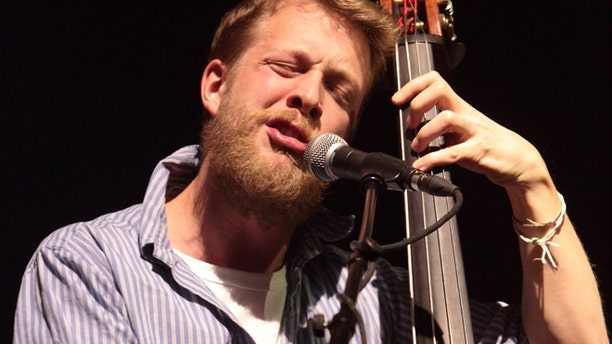 This Feb. 16, 2013 file photo shows Ted Dwane, of the English folk rock band Mumford & Sons, performing at the Susquehanna Bank Center in Camden, N.J. Dwane has a blood clot on his brain that will require surgery.
