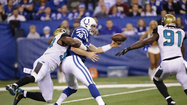 Indianapolis Colts quarterback Andrew Luck (12) fumbles after being hit by Jacksonville Jaguars defensive end Chris Smith (98) during the first half of an NFL football game Sunday, Nov. 23, 2014 in Indianapolis. (AP Photo/AJ Mast)