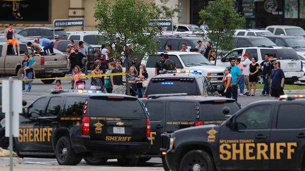 People at the Central Texas MarketPlace watch a crime scene near the parking lot of a Twin Peaks restaurant Sunday, May 17, 2015, in Waco, Texas. (Rod Aydelotte/Waco Tribune-Herald via AP)