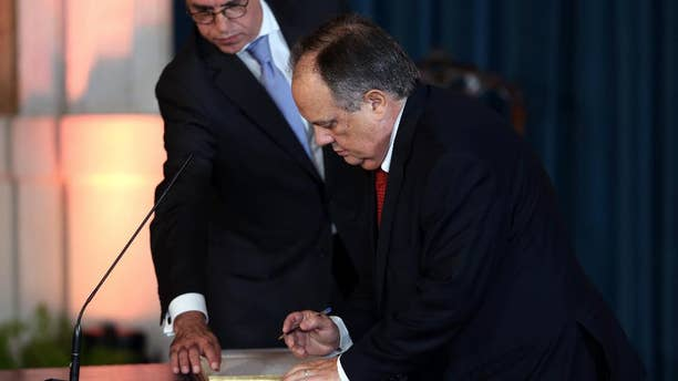 """In this picture taken Nov. 26 2015, Portuguese Culture Minister Joao Soares signs his oath while being sworn in at Lisbon's Ajuda palace. The Portuguese government's head of culture isn't losing his job, despite threatening on social media to slap two newspaper critics. On Thursday, April 7 2016, Prime Minister Antonio Costa said he has reminded members of his government they must be """"reserved in the way they express their emotions,"""" but stopped short of firing Soares. (AP Photo/Armando Franca)"""