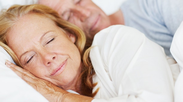 Attractive senior couple lying in bed together and sleeping