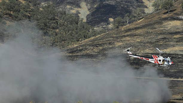 A Cal Fire helicopter flies over the Bear Creek portion of Cache Creek near Clearlake, Calif., Thursday, Aug. 6, 2015. Crews backed by important firefighting resources are gaining ground against a massive Northern California wildfire, but it may be several days before thousands of evacuees can return home, officials said Thursday. (AP Photo/Jeff Chiu)