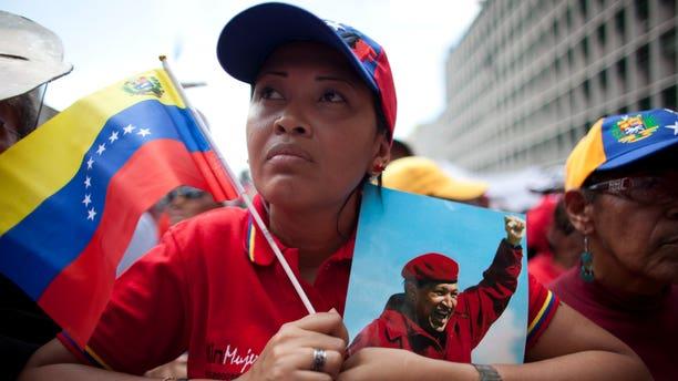Un mujer sostiene una imagen del presidente de Venezuela Hugo Chávez durante una manifestación en Caracas, Venezuela, el miércoles 27 de febrero de 2013. Chávez está batallando por su salud y su vida, afirmó el jueves el vicepresidente Nicolás Maduro, quien aseguró el gobernante enfermó por entregarse a los pobres. (AP foto/Ariana Cubillos)