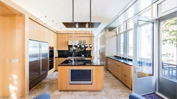The airy, open kitchen features upscale appliances.