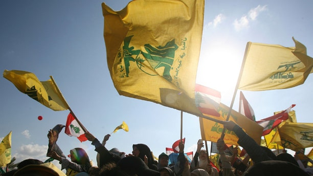 BEIRUT, LEBANON- SEPTEMBER 22: Hezbollah supporters wave flags during a ''Victory over Israel'' rally in Beirut's suburbs on September 22, 2006 in Beirut, Lebanon. Hezbollah leader Sayyed Hassan Nasrallah reportedly said that Hezbollah would not disarm until a Lebanese government capable of protecting the country was in place during the rally.  (Photo by Salah Malkawi/Getty Images)