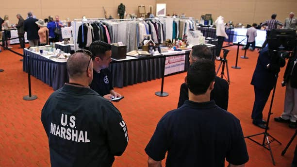 """June 24, 2016: U.S. Marshals keep watch on a room full of personal items belonging to James """"Whitey"""" Bulger and Catherine Greig ahead of a court-ordered auction in Boston."""