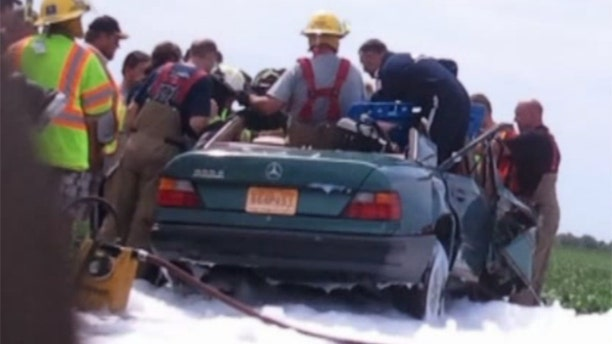 Aug 4, 2013: Firefighters work to rescue a woman from the scene of a car crash in Missouri.