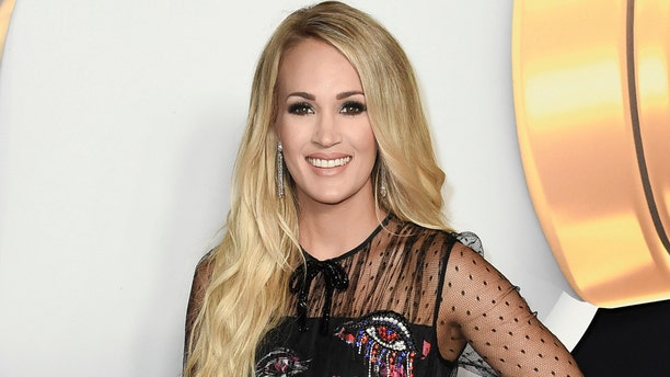 FILE - In this June 22, 2018, file photo, Carrie Underwood attends the 2018 Radio Disney Music Awards in Los Angeles. Underwood says she turned to God after experiencing three miscarriages in the past two years. (Photo by Richard Shotwell/Invision/AP, File)