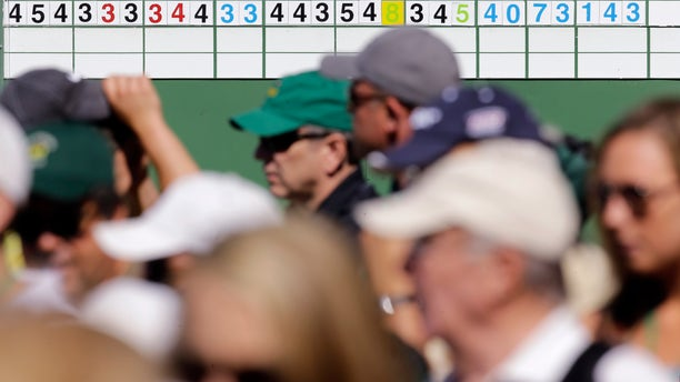 Spectators walk past a leader board displaying Tiger Woods' two first two rounds scores before the third round of the Masters golf tournament Saturday, April 13, 2013, in Augusta, Ga. The score board reflects the 2-stroke penalty assessed to Woods for a drop in 2nd round of the Masters. (AP Photo/Matt Slocum)