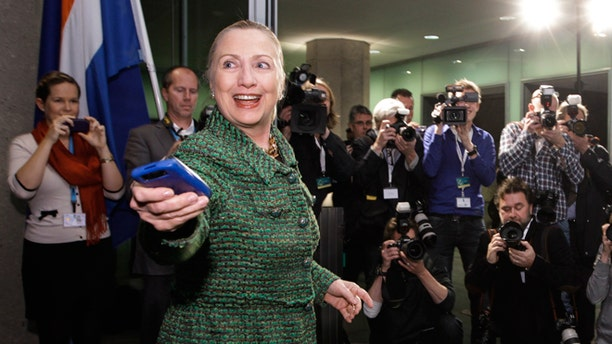 FILE - Dec. 8, 2011: Then-Secretary of State Hillary Rodham Clinton hands off her mobile phone after arriving to meet with Dutch Foreign Minister Uri Rosenthal at the Ministry of Foreign Affairs in The Hague, Netherlands.