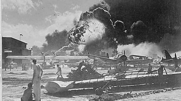 December 7, 1941: Members of the U.S. Military stand near airplane wreckage during the surprise Japanese aerial attack at Naval Air Station at Pearl Harbor in Hawaii.