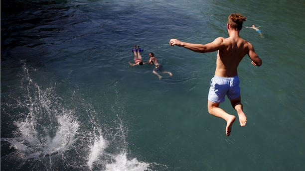 People jump on a hot sunny summer day in the river Aare in Bern, Switzerland, August 6, 2015.