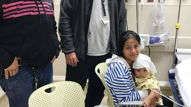 "In this Oct. 14, 2016 photo released by the New York City Police Department, officers Felix Baez, left, and Giovanni Laguna pose for a photo with Liliana Benigno, and her one-year-old baby Ashley Delores, at Lincoln Hospital in The Bronx borough of New York. The officers were on patrol Friday night when they saw the Benigno running with her child down the street yelling ""help"" in Spanish. Seeing that the child was unresponsive, Laguna placed the baby on the ground and began CPR while Baez called for an ambulance. Police say after a minute of CPR, the baby's eyes opened and Laguna felt a faint pulse. (New York City Police Department via AP)"