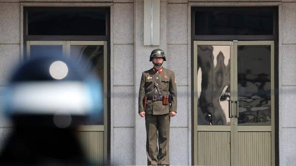 A North Korean soldier looks at the south side as a South Korean soldier stands guard before U.S. Secretary of State Rex Tillerson arrives at the border village of Panmunjom, which has separated the two Koreas since the Korean War.