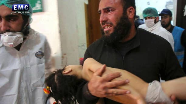 A man carries his child into a hospital following a chemical attack in Syria in April.