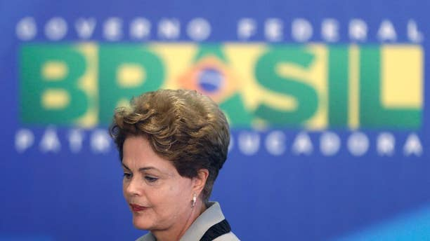 Brazil's President Dilma Rousseff leaves at the end of a government ceremony at the Planalto presidential palace in Brasilia, Brazil, Monday, March 16, 2015. Massive protests calling for Rousseff's impeachment on Sunday have narrowed her options to fend off political and economic crises, but her ouster remains highly unlikely, analysts said Monday. (AP Photo/Eraldo Peres)