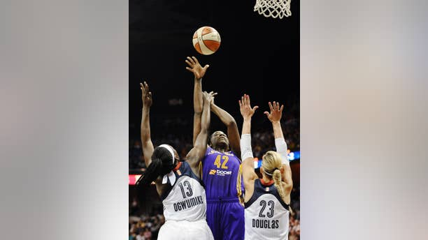 Los Angeles Sparks' Jantel Lavender, center, shoots as Connecticut Sun's Chiney Ogwumike, left, and Katie Douglas, right, defend during the first half of a WNBA basketball game, Sunday, July 13, 2014, in Uncasville, Conn. (AP Photo/Jessica Hill)