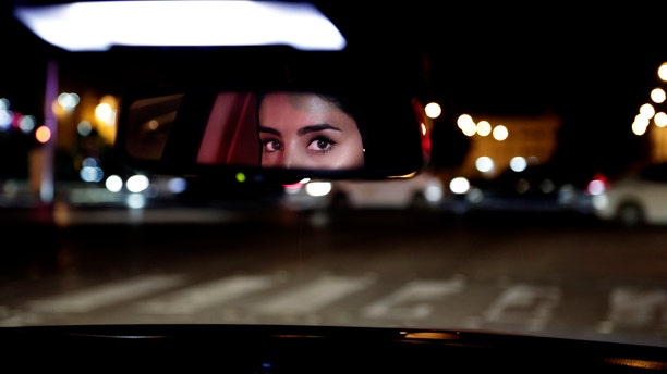 In this Sunday, June 24, 2018 file photo, Hessah al-Ajaji drives her car down the capital's busy Tahlia Street after midnight for the first time, in Riyadh, Saudi Arabia.