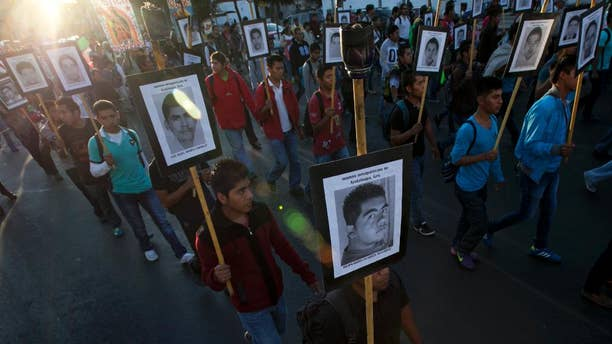 FILE - In this Dec. 26, 2015, file photo, relatives of the 43 missing students from the Isidro Burgos rural teachers college march holding pictures of their missing loved ones during a protest in Mexico City. A third investigation of a dump site in southern Mexico found evidence indicating there was a large fire there in which at least 17 people were burned, a member of a six-person fire expert team said Friday, April 1, 2016. (AP Photo/Marco Ugarte, File)