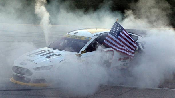 Brad Keselowski (2) celebrates his win with a burnout after winning the NASCAR Sprint Cup series auto race at Chicagoland Speedway in Joliet, Ill., Sunday, Sept. 14, 2014. (AP Photo/Paul J. Bergstrom)