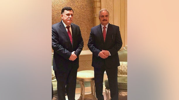 "In this Tuesday, May 2, 2017, photo supplied by the Libyan armed forces, Tripoli-based Prime Minister Fayez Serraj, left, poses for a photograph with Field Marshal Khalifa Hifter, right, in Abu Dhabi, United Arab Emirates. The two met Tuesday in the UAE capital for what the Libyan military described as ""Arab and international mediation"" over that country's long political crisis. (Libyan armed forces via AP)"
