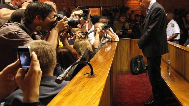 File - In this Wednesday, Feb. 20, 2013 file photo Olympic athlete Oscar Pistorius stands inside a court during his bail hearing at the magistrate court in Pretoria, South Africa. Pistorius will defend himself March 3, 2014 against a charge of premeditated murder in the slaying of his girlfriend Reeva Steenkamp. A South Africa judge has ruled that television stations can broadcast parts of the trial live, but with restrictions on witness testimonies.  (AP Photo/Themba Hadebe, File)