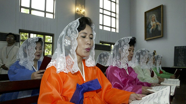 """North Koreans read mass at one the """"official"""" Catholic churches in Pyongyang. While religious freedom is part of the North Korean constitution, Christians must conceal their faith or risk death by the regime."""