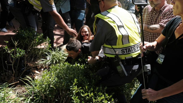 Police pictured helping Jason Kessler after he was chased off by protesters during his press conference Sunday.