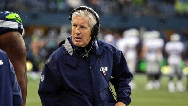 Seattle Seahawks head coach Pete Carroll wears a headset as he walks on the sideline during the second half of an NFL football game against the Oakland Raiders, Sunday, Nov. 2, 2014, in Seattle. (AP Photo/Elaine Thompson)