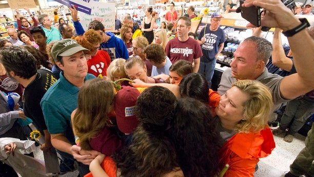 """A few protesters hug as they hold a """"die-in"""" protest at a Publix supermarket on Friday, May 25, 2018."""