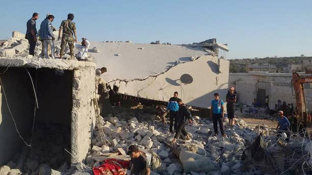 FILE - In this Tuesday Sept. 23, 2014 file photo provided by an anti-Bashar Assad activist group Edlib News Network (ENN), which has been authenticated based on its contents and other AP reporting, Syrian citizens check a damaged house that they say was targeted by the coalition airstrikes in the village of Kfar Derian, a base for the al-Qaida-linked Nusra Front, a rival of the Islamic State group, between the northern province of Aleppo and Idlib, Syria. U.S.-led coalition airstrikes against the Islamic State group and other extremists in Syria have killed more than 860 people, including civilians, since they began in mid-September, a monitoring group said Wednesday, Nov. 12. (AP Photo/Edlib News Network ENN, File)