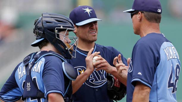 Tampa Bay Rays starting pitcher Matt Moore, center, talks with pitching coach Jim Hickey (48) and catcher Ryan Hanigan (24) in the third inning of an exhibition baseball game against the Boston Red Sox in Fort Myers, Fla., Sunday, March 23, 2014. THe Rays won 9-2. (AP Photo/Gerald Herbert)