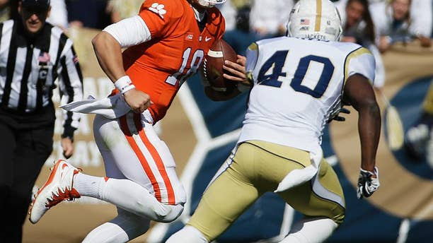 Clemson quarterback Cole Stoudt, left, is chased while running the ball by Georgia Tech's Paul Davis in the second quarter of an NCAA college football game, Saturday, Nov. 15, 2014, in Atlanta. Georgia Tech won 28-6. (AP Photo/David Goldman)