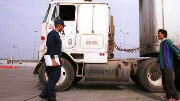 File Photo: Mario Leal, a U.S. Department of Transportation border inspector, explains his evaluation of a Mexican driver's big rig truck in Laredo, TX. The D.O.T. inspectors check trucks for safety violations as they enter the United States from Mexico. (Photo by Joe Raedle/Newsmakers)
