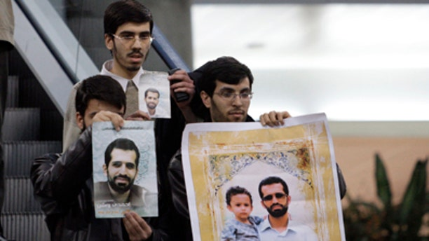 Jan. 29, 2012: An Iranian protester holds a placard against Israel and International Atomic Energy Organization, IAEA, at the Imam Khomeini airport, waiting for arrival of the agency's delegates, who were not appeared in public, as the others hold posters of Mostafa Ahmadi Roshan, a chemistry expert and director of the Natanz uranium enrichment facility in central Iran, who was killed in a bomb attack in Tehran earlier this month.